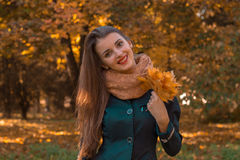 Cheerful beautiful girl with long hair and a warm scarf keeps its leaves in his hand  smiles Stock Image