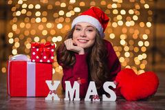 Cheerful beautiful girl lying near letters spelling word Xmas Stock Photos