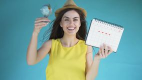 Vacation is coming. Cheerful beautiful girl in stylish sunhat holding calender and the small globe, expressing huge joy about upcoming vacation, isolated shot in stock footage
