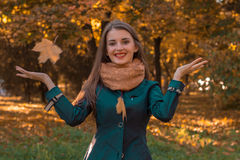 Cheerful beautiful girl throws the leaves in the Park and laughs Stock Photos
