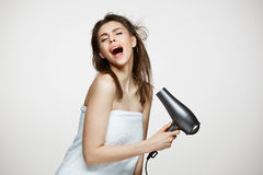 Cheerful beautiful girl in towel smiling laughing singing with hair dryer making funny face over white background stock photos