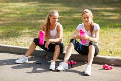 Smiling pretty girls sitting with water after training on a natural background. Relaxing sports concept. Stock Image