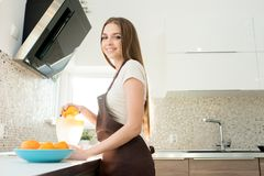 Cheerful beautiful housewife making fresh orange juice royalty free stock photos