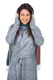 Cheerful beautiful model wearing winter clothes listening to mus Royalty Free Stock Images