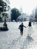 Cheerful beautiful newlywed couple is holding hands while running along the sunny town street. Vertical back view. Cheerful beautiful newlywed couple is holding Stock Photos