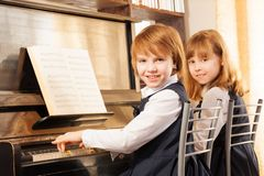 Cheerful beautiful small girls play piano together. Cheerful beautiful small girls playing piano together with notes during lesson Stock Photography