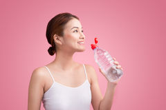 Cheerful beautiful sporty asian young woman holding a bottle of Stock Photography