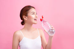 Cheerful beautiful sporty asian young woman holding a bottle of Royalty Free Stock Images