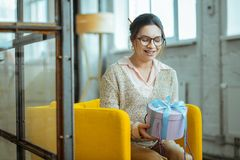 Cheerful beautiful woman feeling satisfied holding present box stock image