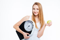 Cheerful beautiful  woman holding scales and green apple. Cheerful beautiful young woman holding scales and green apple over white background Royalty Free Stock Photos