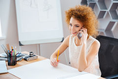 Cheerful beautiful woman photographer sitting and talking on mobile phone Royalty Free Stock Photos