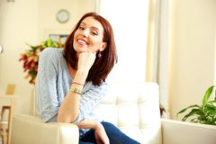 Cheerful beautiful woman sitting on the sofa Royalty Free Stock Image