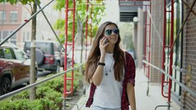 Cheerful beautiful woman in stylish glasses and trendy outfit has phone conversation and strolling on the street. Satisfied young girl in sunglasses and stylish stock video