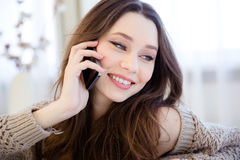 Cheerful beautiful woman talking on mobile phone at home Stock Images