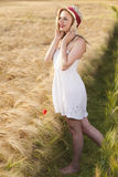 Cheerful beautiful young blonde girl in white dress with straw h Royalty Free Stock Photography