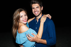Cheerful beautiful young couple standing on the beach at night. Portrait of cheerful beautiful young couple standing on the beach at night royalty free stock photography