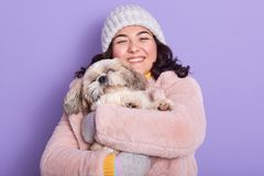 Free Cheerful Beautiful Young Girl Holding Her Dog In Both Hands, Hugging Pet Much, Being Fond Of Animals, Wearing Pink Faux Fur Coat Royalty Free Stock Photo - 164799495