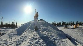 Cheerful beautiful young girl snowboarder does a trick on a snowboard on a diving board. Bounces and falls in the snow. Rides on a winter board. Winter fun at stock video footage