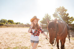 Cheerful beautiful young woman cowgirl with her horse on ranch Stock Photo