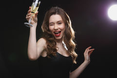 Cheerful beautiful young woman drinking champagne royalty free stock images