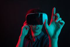 Cheerful beautiful young woman entertained with virtual reality helmet in studio and colorful lighting. Young woman using modern technology. Woman with virtual royalty free stock images