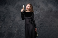Cheerful beautiful young woman holding bottle and glass of champagne Stock Photography