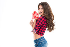 Cheerful beautiful young woman holding heart shaped candy and smiling Royalty Free Stock Photos