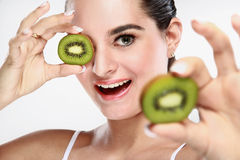 Cheerful beautiful young woman with kiwi fruit in her hands Royalty Free Stock Photo