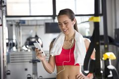 Cheerful beautiful young woman listening music in the gym. Cheerful beautiful young woman listening to music in the gym Royalty Free Stock Photos