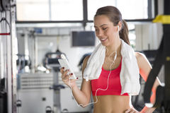Cheerful beautiful young woman  listening to music. In the gym Stock Photography