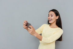 Cheerful beautiful young woman playing video games on mobile phone stock photos