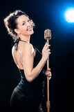 Cheerful beautiful young woman singer holding golden vintage mic Stock Photography