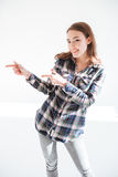 Cheerful beautiful young woman standing and pointing away stock image