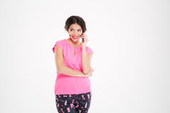Cheerful beautiul young woman standing and talking on cell phone Royalty Free Stock Image