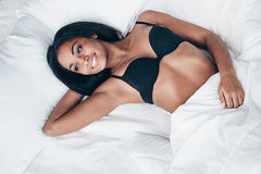 Cheerful beauty in bed. Top view of beautiful young African woman in black lingerie lying in bed with smile Stock Images