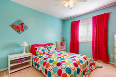 Cheerful bedroom interior in turquoise color. With bright red curtains and colorful bedding Stock Images