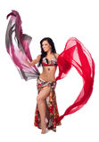 Cheerful Belly Dancer Dancing with Multicolored Veils. A beautiful bellydancer in a multicolor costume smiles as she dances with two colorful, flowing, silk Royalty Free Stock Image