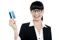 Cheerful bespectacled woman holding up cash card Stock Photo