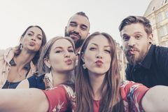 Cheerful best friends in the city take a selfie making duckface kiss expression Stock Image