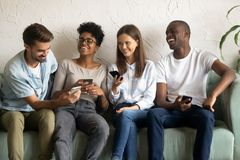 Friends laughing together watching video on smartphones stock image