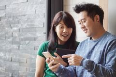 Cheerful best friends viewing funny photos in social networks via smartphone standing together. Selective focus. Copy space. royalty free stock photo