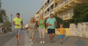 Cheerful big family going in for sport together. Steadicam shot of parents, child and grandparents jogging along the waterfront at sunset. Family keeping healthy stock video footage