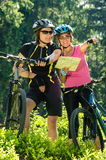 Cheerful bikers checking the map. Young cheerful bikers checking the map sunny day in nature Royalty Free Stock Photography