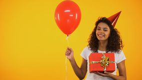 Cheerful biracial girl holding giftbox and balloon, celebrating birthday party. Stock footage stock video footage