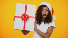 Cheerful biracial girl in santa claus hat saying Wow and showing huge giftbox. Stock footage stock video