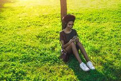 Cheerful black girl with cellphone sitting on the grass stock photo
