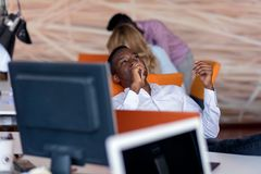 Cheerful black guy is watching at his laptop screen, at his work place, with arms behind the head. Cheerful black guy is watching at his laptop screen, at his Stock Images