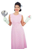 Cheerful black hair model holding a pan and wearing rubber glove Stock Photo