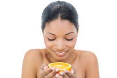 Cheerful black haired model holding orange slice Royalty Free Stock Photo