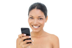 Cheerful black haired model text messaging Stock Photography